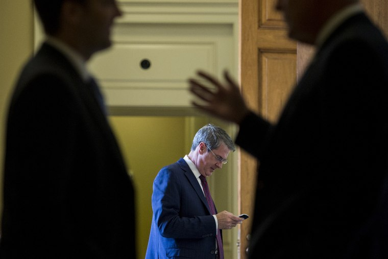 Sen. David Vitter, R-La., center, talks on his cell phone as two Senators in the foreground talk outside of the Senate Republicans' policy lunch in the Capitol on April 21, 2015 in Washington, D.C. (Photo By Bill Clark/CQ Roll Call/Getty)