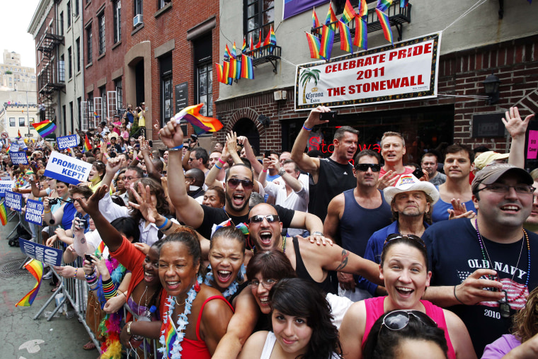 People cheer while standing in front of the Stonewall Inn on Christopher Street in Greenwich Village as the annual Gay Pride parade passes, June 26, 2011 in New York, N.Y. (Photo by Mark Lennihan/AP)