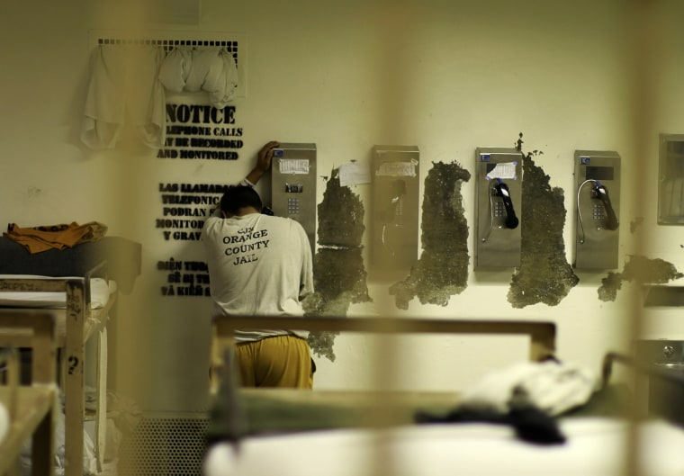 An inmate makes a phone call from his cell at the Orange County jail in Santa Ana, Calif., May 24, 2011. (Photo by Lucy Nicholson/Reuters)