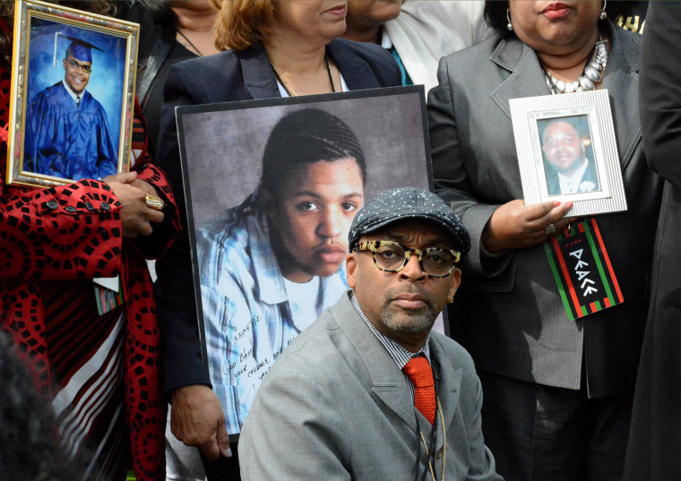 Filmmaker Spike Lee appears at a news conference, May 14, 2015 in Chicago, flanked by parents holding photographs of the children they've lost to gun violence in Chicago. (Photo by Brian Jackson/Sun-Times Media/AP)