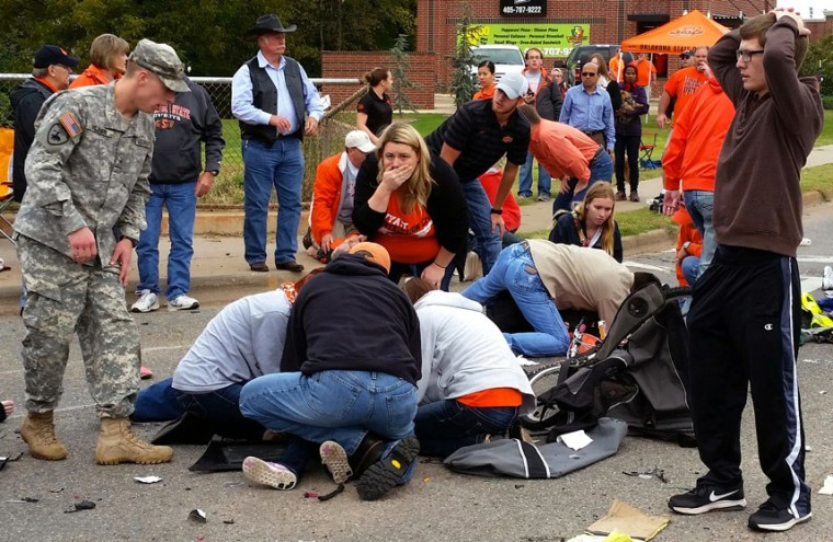 Bystanders help the injured after a vehicle crashed into a crowd of spectators during the Oklahoma State University homecoming parade, causing multiple injuries, Oct. 24, 2015 in Stillwater, Oka. (Photo by David Bitton/The News Press/AP)