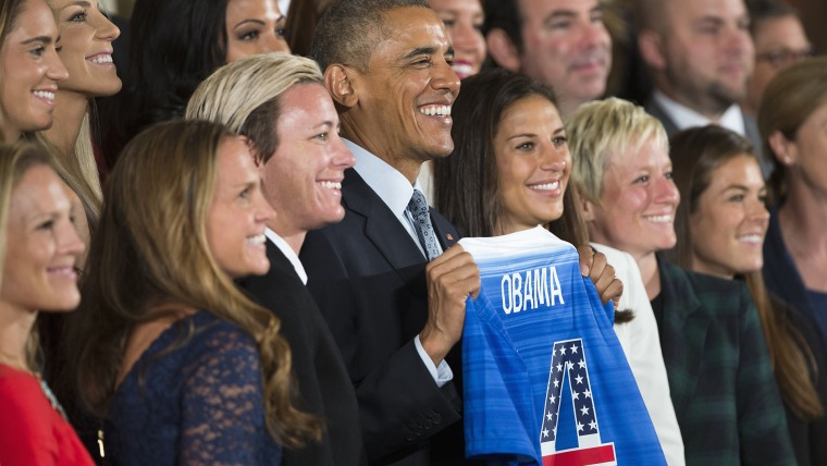 President Barack Obama holds a jersey and poses for photographs during a ceremony to honor the 2015 FIFA Women's World Cup champion U.S. National Soccer Team, Oct. 27, 2015, in the East Room of the White House in Washington, D.C. (Photo by Evan Vucci/AP)
