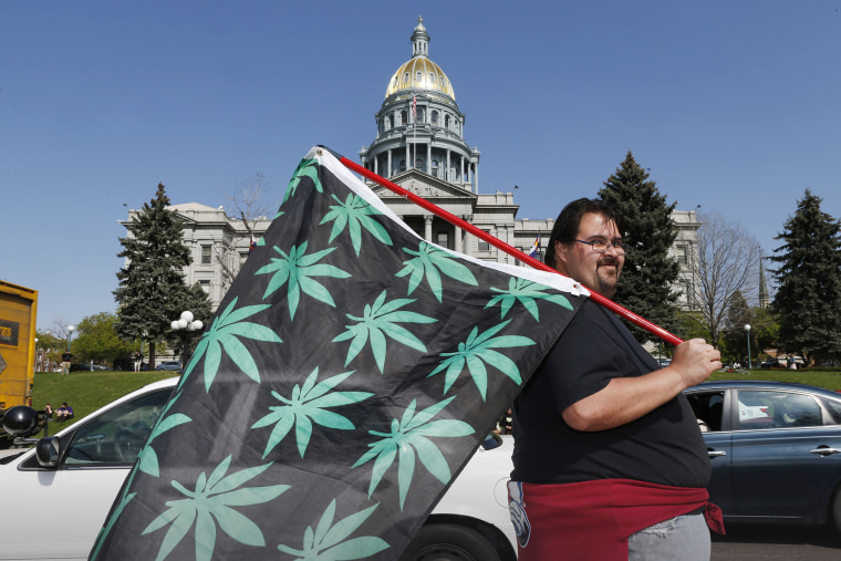 Kris Custer of Denver waves a flag in support of marijuana in front of the State Capitol, April 20, 2015, in Denver, Co. (Photo by David Zalubowski/AP)