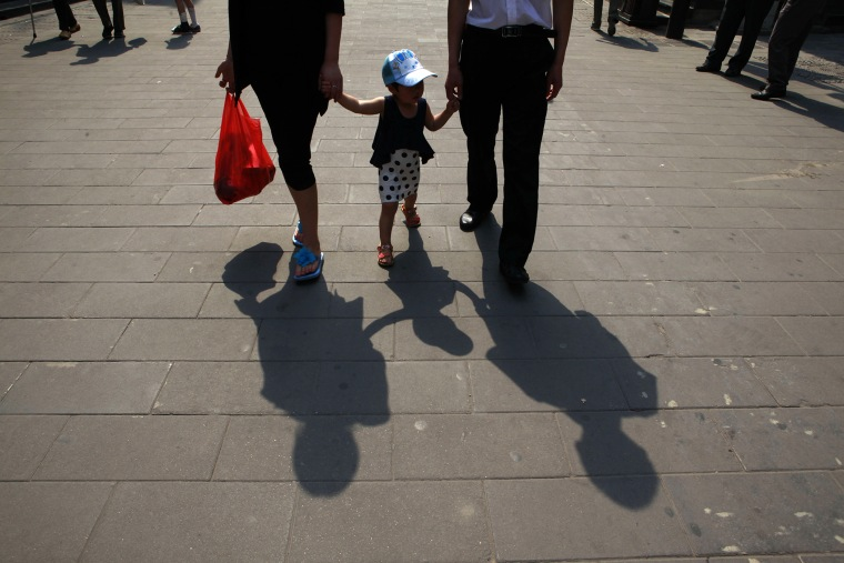 A couple hold hands with a child along a retail street in Beijing, China. (Photo by Ng Han Guan/AP)