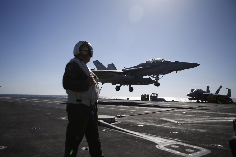 A U.S. Navy crew member looks at an F/A-18 Super Hornet fighter landing onto the deck of the USS Ronald Reagan, during a joint naval drill between South Korea and the U.S. in the West Sea, South Korea, Oct. 28, 2015. (Photo by Kim Hong-ji/Pool/AP)