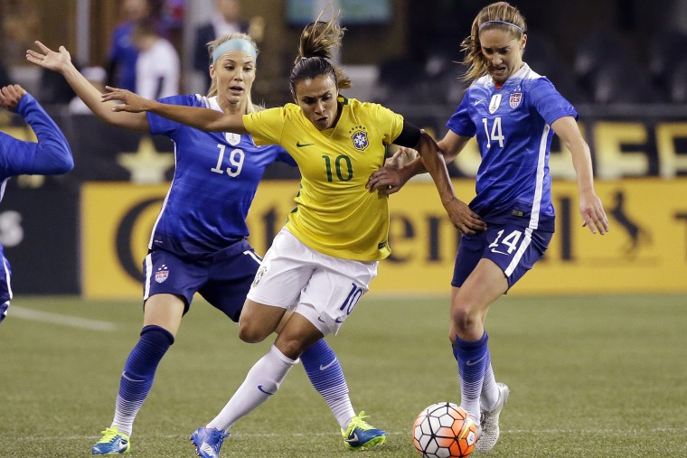 Brazil's Marta (10) works to get to the ball between the United States' Julie Johnston (19) and Morgan Brian (14) during the first half of an international friendly soccer match, Oct. 21, 2015, in Seattle. (Photo by Elaine Thompson/AP)