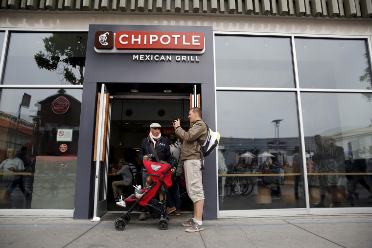 A man snaps a photograph at the entrance to Chipotle Mexican Grill in San Francisco, Calif., July 21, 2015. (Photo by Robert Galbraith/Reuters)