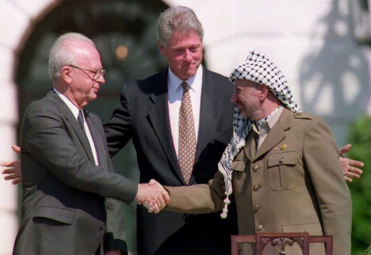 US President Bill Clinton stands between PLO leader Yasser Arafat and Israeli Prime Minister Yitzahk Rabin as they shake hands on Sep. 13, 1993 at the White House in Washington DC. (Photo by J. David Ake/AFP/Getty)