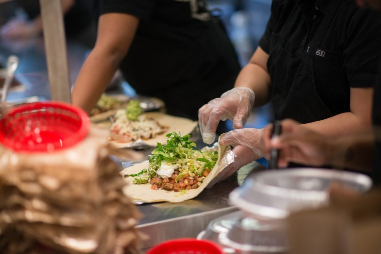 Employees prepare lunch orders at a Chipotle Mexican Grill restaurant. (Photo by Craig Warga/Bloomberg/Getty)