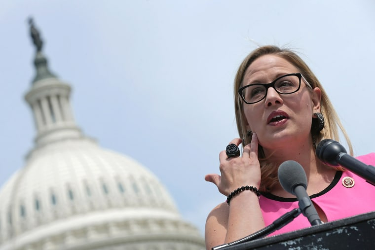 Rep. Kyrsten Sinema (D-AZ) (C) joins a group of bipartisan Congressmen during a news conference outside the U.S. Capitol, May 20, 2014 in Washington, D.C. (Photo by Chip Somodevilla/Getty)