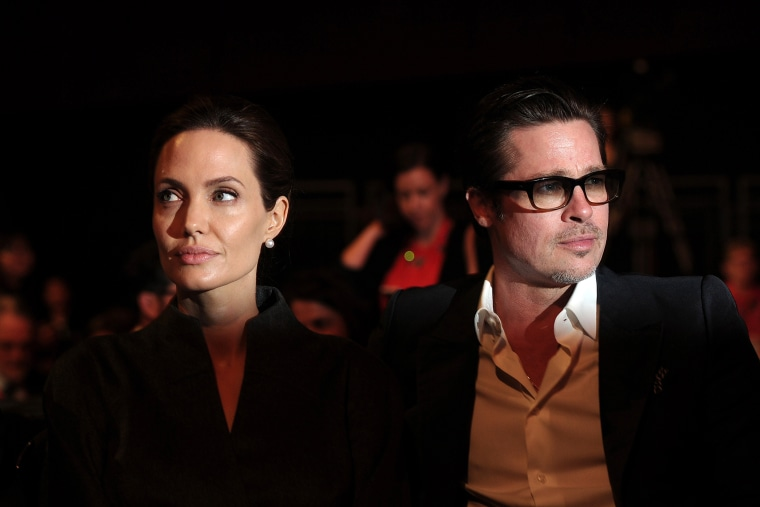 Angelina Jolie (L) and her husband Brad Pitt attend the fourth day of the Global Summit to End Sexual Violence in Conflict in London on June 13, 2014. (Photo by Carl Court/AFP/Getty)