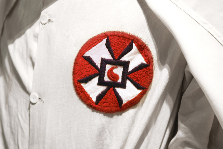 A photo illustration of a Ku Klux Klan member in white robe and hood. (Photo by Peter Dazeley/Getty)
