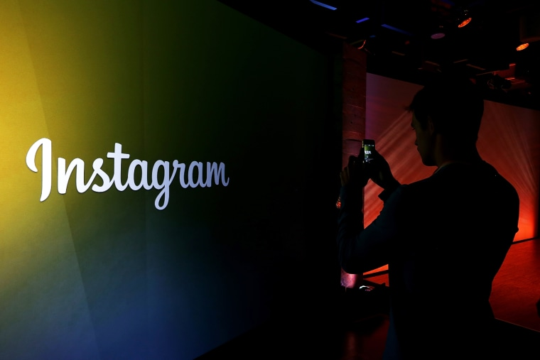 An attendee takes a photo of the Instagram logo during a press event. (Photo by Justin Sullivan/Getty)