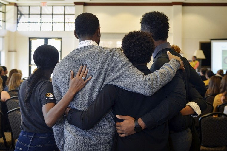 In this Saturday, Nov. 7, 2015, photo, members of an anti-racism and black awareness group embrace during a protest in the University of Missouri campus in Columbia, Mo. (Photo by Ellise Verheyen/Missourian/AP)