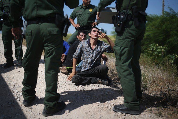 U.S. Border Patrol agents detain undocumented immigrants after they crossed the border from Mexico into the United States on Aug. 7, 2015 in McAllen, Texas. (Photo by John Moore/Getty)