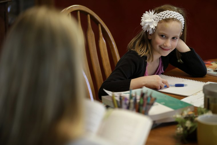 Abigail Gustoff listens to her mom Sara read while home schooling at the kitchen table in in their home in Des Moines, Ia., April 18, 2013. (Photo by Charlie Neibergall/AP)