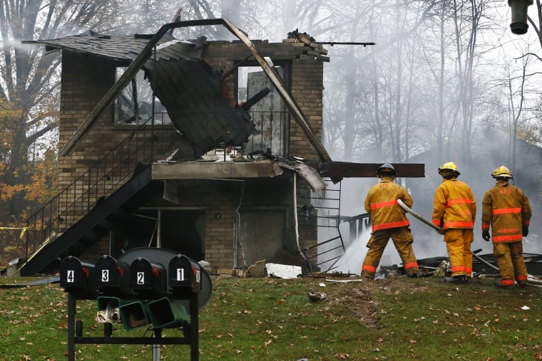 Firefighters work at the scene where authorities say a small business jet crashed into an apartment building in Akron, Ohio, Tuesday, Nov. 10, 2015. (Photo by Ed Suba Jr./Akron Beacon Journal/AP)