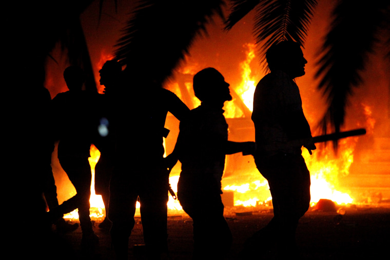 In this Friday, Sept. 21, 2012 file photo, Libyan civilians watch fires at an Ansar al-Shariah Brigades compound, after hundreds of Libyans, Libyan Military, and Police raided the Brigades base, in Benghazi, Libya. (Photo by Mohammad Hannon/AP)