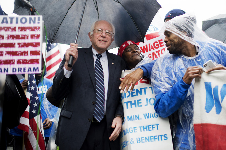 On the day of a Republican presidential debate, Sen. Bernie Sanders, I-Vt., attends a rally in Upper Senate Park with striking workers to call for a minimum wage of $15 per hour, Nov. 10, 2015. (Photo By Tom Williams/CQ Roll Call/AP)