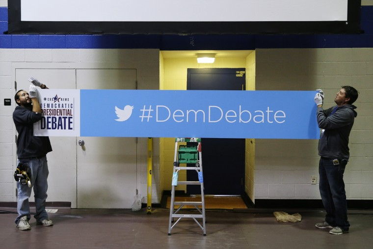 Workers Daniel Rodriguez, left, and Chad Parson hang a sign in the media filing center before Saturday night's Democratic Presidential Debate, Nov. 13, 2015, in Des Moines, Iowa. (Photo by Charlie Neibergall/AP)