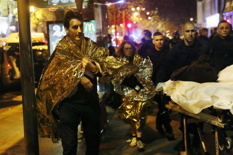 Victims walk away outside the Bataclan theater in Paris, Nov. 13, 2015. (Photo by Jerome Delay/AP)