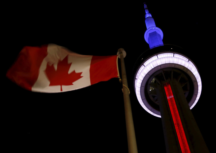 The landmark CN Tower is lit blue, white and red in the colors of the French flag following Paris attacks, in Toronto, Nov. 13, 2015. (Photo by Chris Helgren/Reuters)