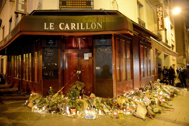 Flowers and candles are placed outside Le Carillon bar, the day after a deadly attack on Nov. 14, 2015 in Paris, France. (Photo by Antoine Antoniol/Getty)
