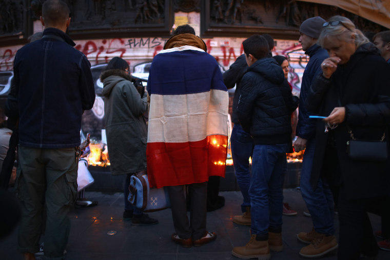 Parisians light candles and lay tributes on the monument at Place de la Republique, the day after deadly terrorist attacks on Nov. 14, 2015 in Paris, France. (Photo by Christopher Furlong/Getty)