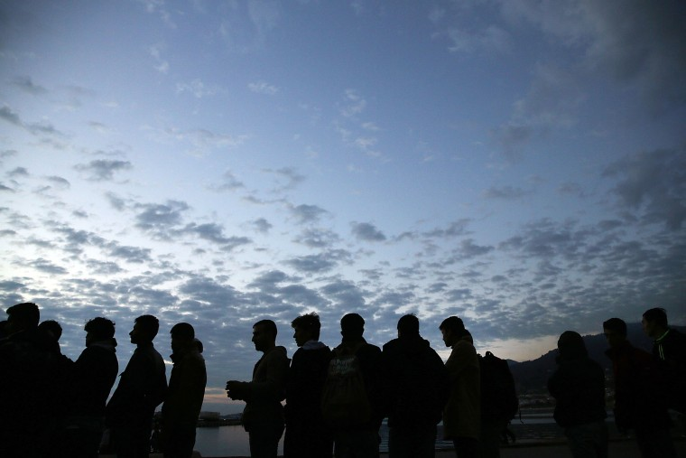 Iraqi, Syrian and Afghan refugees wait in line at dawn for a ferry to Athens after they arrived on the island of Lesbos in a raft from Turkey on Oct. 13, 2015 in Mitilini, Greece. (Photo by Spencer Platt/Getty)