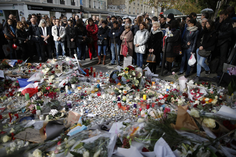People observe a minute of silence outside the Bataclan music hall to pay tribute to the victims of the series of deadly attacks, in Paris, France, Nov. 16, 2015. (Photo by Christian Hartmann/Reuters)