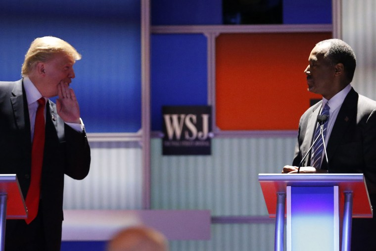 Republican U.S. presidential candidate and businessman Donald Trump whispers across to Dr. Ben Carson during a debate held in Milwaukee, Wis., Nov. 10, 2015. (Photo by Jim Young/Reuters)