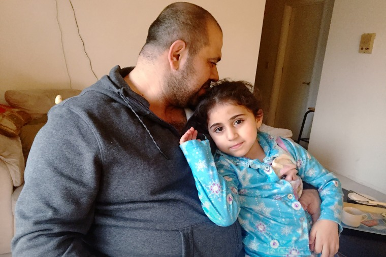 Amjad and his daughter rest in their home in Ohio. (Photo by Amanda Sakuma)