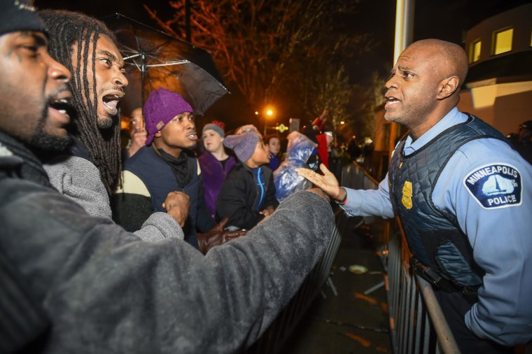 A police officer talks with demonstrators in front of a north Minneapolis police precinct during a protest in response of Sunday's shooting death of Jamar Clark by police officers in Minneapolis, Minn., Nov. 18, 2015. (Photo by Craig Lassig/Reuters)
