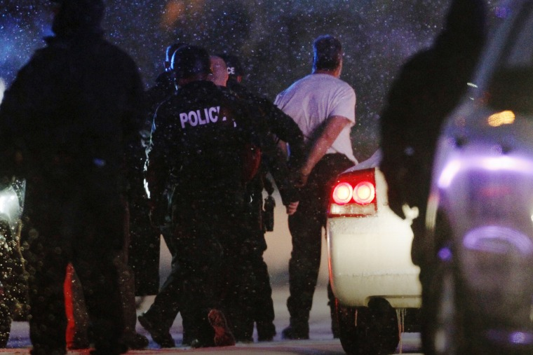 The handcuffed suspected gunman at the Planned Parenthood clinic is moved to a police vehicle in Colorado Springs, Colo., Nov. 27, 2015. (Photo by Rick Wilking/Reuters)