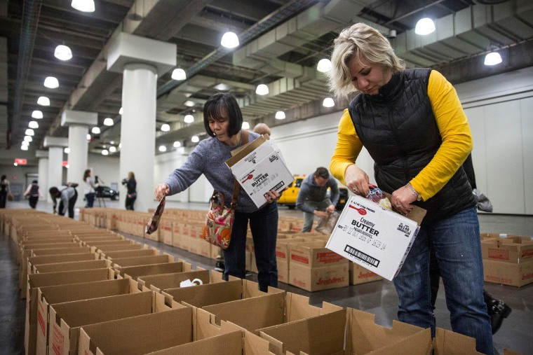 Volunteers distribute donated food into Thanksgiving meal boxes on Nov. 23, 2015 in New York City. The free meals were organized by the state government through a food drive and given to those in need for Thanksgiving. (Photo by Andrew Burton/Getty)