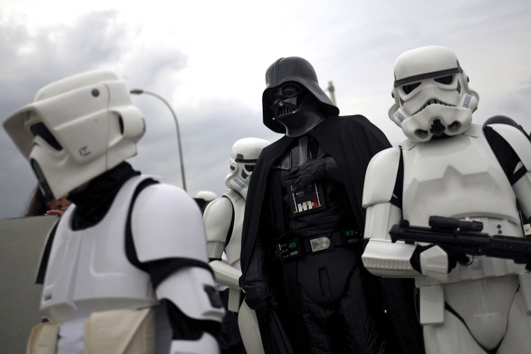 """People dress up as """"Darth Vader"""" (C) and """"Stormtroopers"""" from the movie """"Star Wars."""" (Photo by Jon Nazca/Reuters)"""