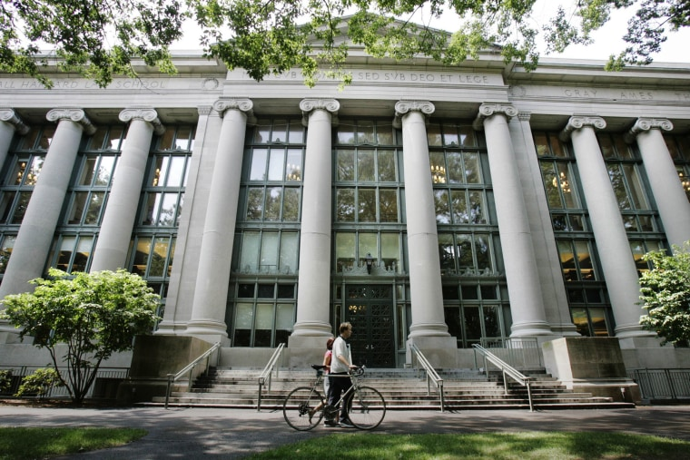 A bicyclist walks by Langdell Hall, the Harvard Law Library, on the campus of the Harvard Law School in Cambridge, Mass., Aug. 1, 2005. (Photo by Charles Krupa/AP)