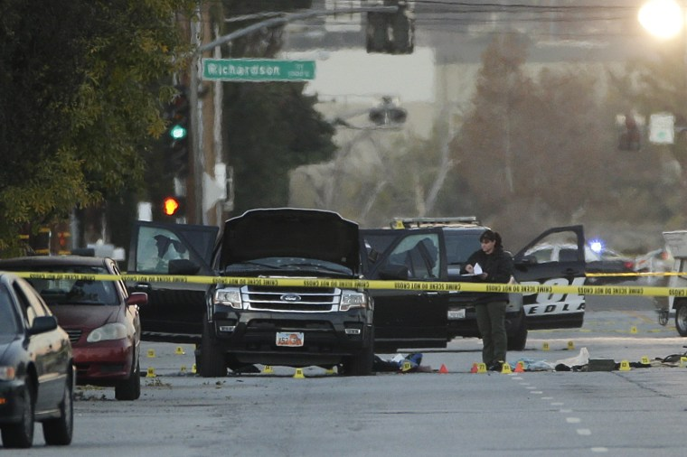 An investigator looks at a black SUV that was involved in a police shootout with suspects, Dec. 3, 2015, in San Bernardino, Calif. A heavily armed man and...