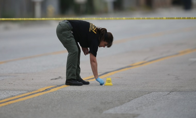 A Law enforcement officer picks up as shell casing near the Ford SUV vehicle that was the scene where suspects of the shooting at the Inland Regional Center were killed on Dec. 4, 2015 in San Bernardino, Calif. (Photo by Joe Raedle/Getty)