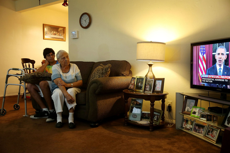 Jonathan Tovar and his grandmother Helen Medina in her house, which was hit by bullets in a gun battle between police and terror suspects, watch President Obama's address, Dec. 6, 2015 in San Bernardino, Calif. (Photo by Joe Raedle/Getty)