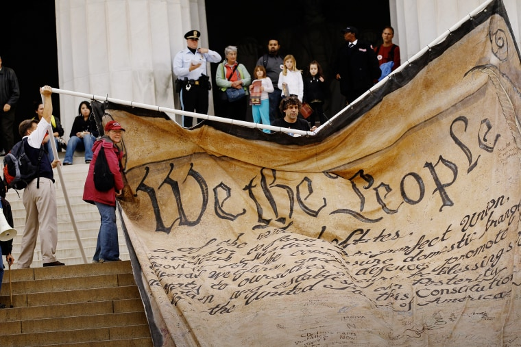 Volunteers unfurl a giant banner printed with the Preamble to the United States Constitution during a demonstration at the Lincoln Memorial on the National Mall Oct. 20, 2010 in Washington, DC. (Photo by Chip Somodevilla/Getty)