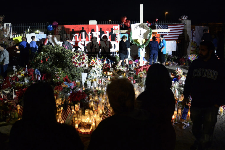 People gather around a makeshift memorial outside the Inland Regional Center where Syed Farook and wife Tashfeen Malik shot and killed 14 people, in San Bernardino, Calif., Dec. 7, 2015. (Photo by Mike Nelson/EPA)