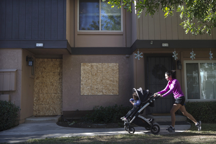 A woman pushes a baby stroller past the boarded-up townhouse rented by San Bernardino shooting rampage suspects Syed Farook and his wife, Tashfeen Malik, Saturday, Dec. 5, 2015, in Redlands, Calif. (Photo by Jae C. Hong/AP)