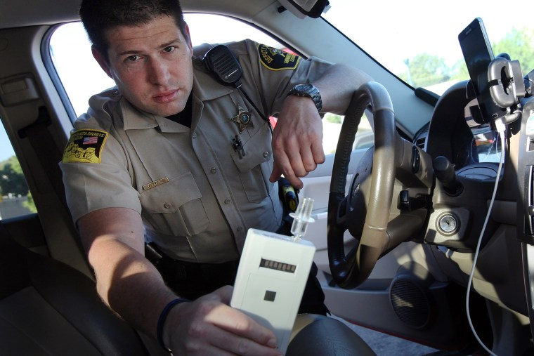 In this Sept. 21, 2015 photo, Minnehaha County Deputy Sheriff Elliott Crayne installs a car breathlyzer outside the county jail in Sioux Falls, S.D. (Photo by Jay Pickthorn/AP)