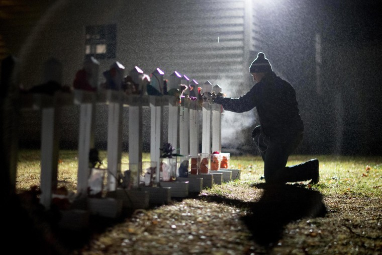 A man adjusts a display of wooden crosses, and a Jewish Star of David, representing the victims of the Sandy Hook Elementary School shooting, on his front lawn, Dec. 17, 2012, in Newtown, Conn. (Photo by David Goldman/AP)