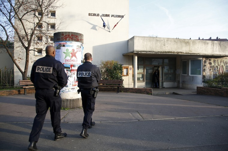 French police stand in front of the nursery school where a teacher claimed to have been assaulted by a hooded man with a knife, reportedly acting for Islamic State in Aubervilliers, near Paris, France, Dec. 14, 2015. (Photo by Charles Platiau/Reuters)