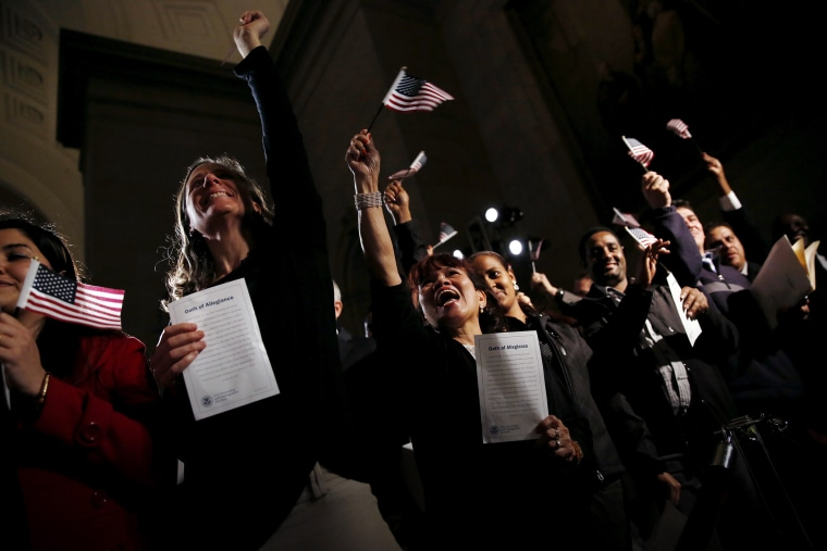 People celebrate as they become U.S. citizens during a naturalization ceremony at the National Archives Museum in Washington, Dec. 15, 2015. (Photo by Carlos Barria/Reuters)