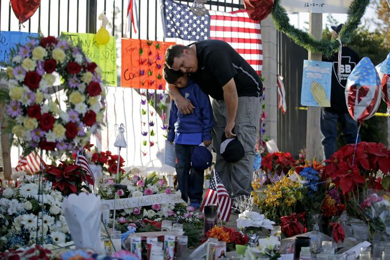 Gary Mendoza, and his son Michael pay their respects at a makeshift memorial site honoring shooting victims, in San Bernardino, Calif. (Photo by Jae C. Hong, File/AP)