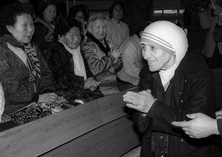 Mother Teresa is welcomed by aged women lepers on arriving at St. Lazarus Leprosy Village's church in Shinhung, Korea