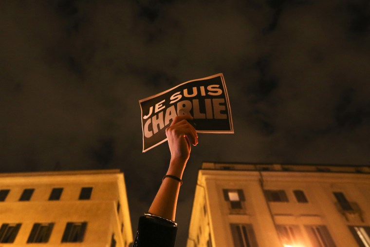 """A woman holds a placard reading """"I am Charlie,"""" to pay tribute to victims following a shooting at the offices of weekly newspaper Charlie Hebdo in Paris, in front of the French embassy in Rome, Jan. 8, 2015. (Photo by Alessandro Bianchi/Reuters)"""